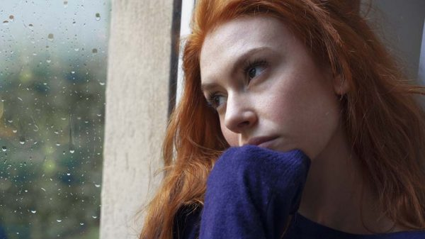 Junge Frau schaut traurig aus dem Fenster.