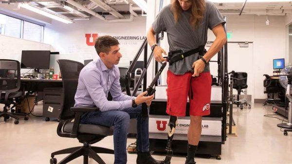 Wissenschaftler Tommaso Lenzi (l.) legt einem Probanden das Exoskelett an.