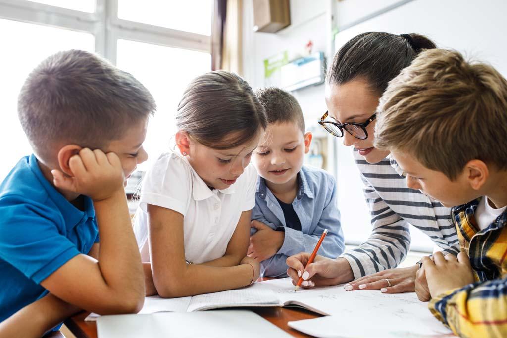 Lehrerin erklärt Grundschülern eine Aufgabe im Klassenzimmer.