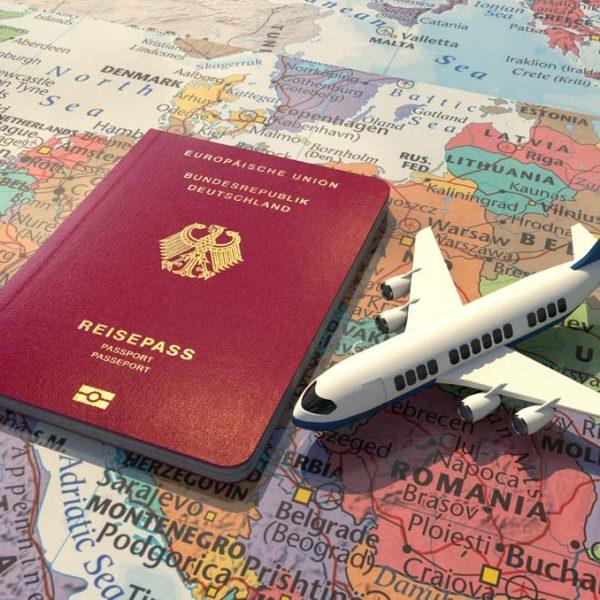 Deutscher Reisepass und Spielzeug-Flugzeug auf einer Europa-Karte