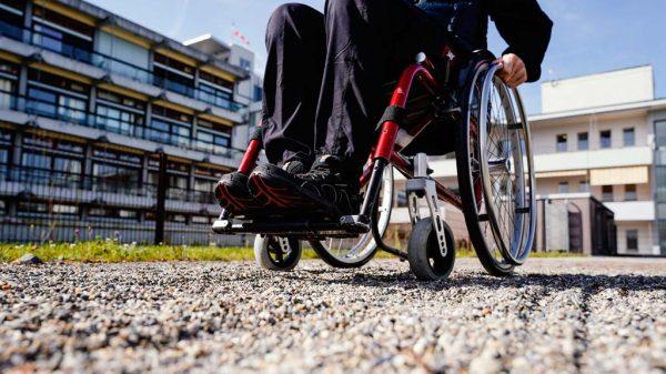 Andreas Brandl fährt im SRH Klinikum Karlsbad-Langensteinbach in einem Rollstuhl-Parcours mit seinem Rollstuhl über einen Kiesweg.
