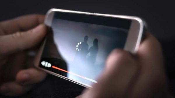 Mann schaut Video auf dem Handy an, das Video stockt bei der Wiedergabe.