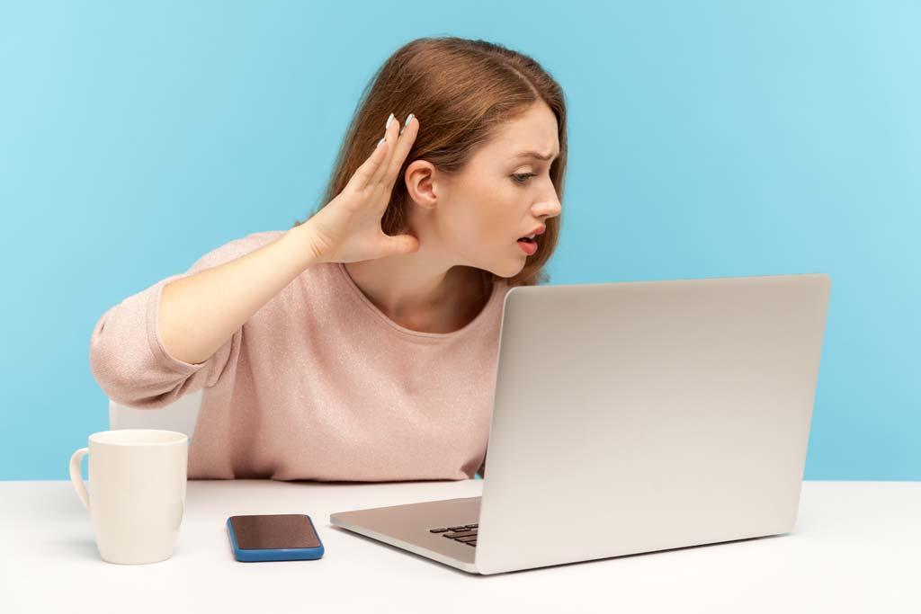 Frau am Laptop hält ihre Hand ans Ohr.