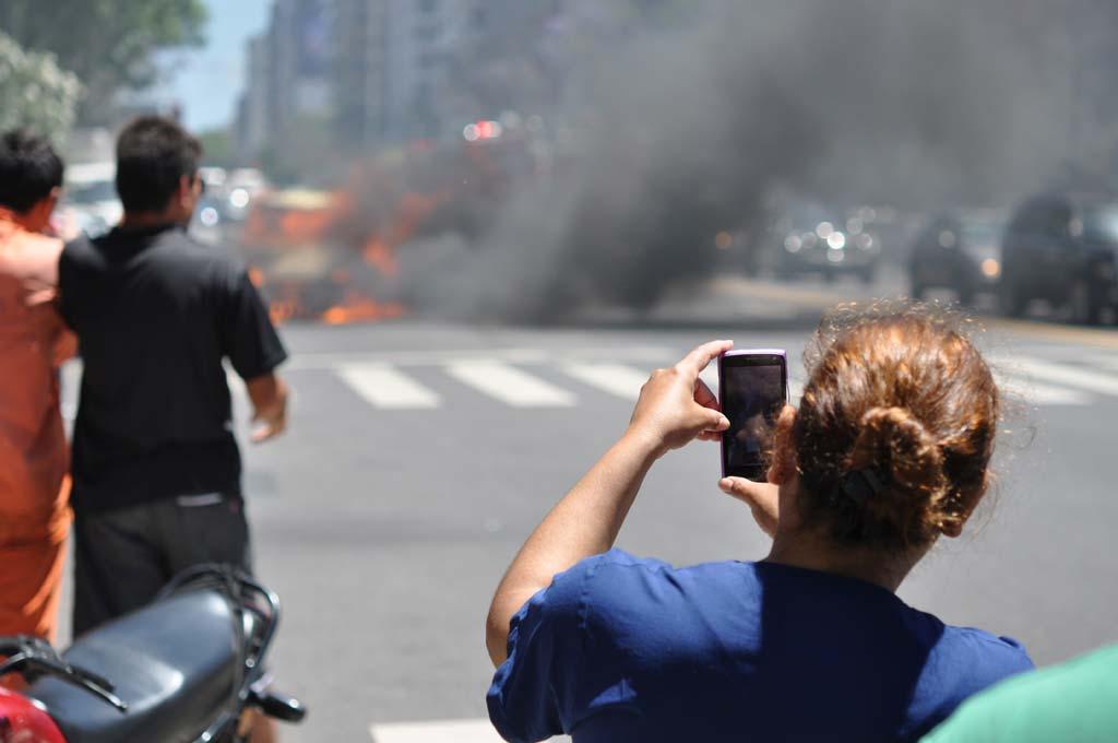 Schaulustige fotografiert einen Verkehrsunfall.
