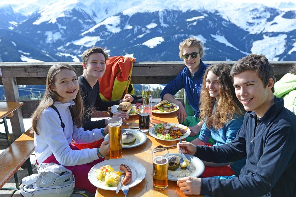 Junge Erwachsene essen auf einer Berghütte zu Mittag.